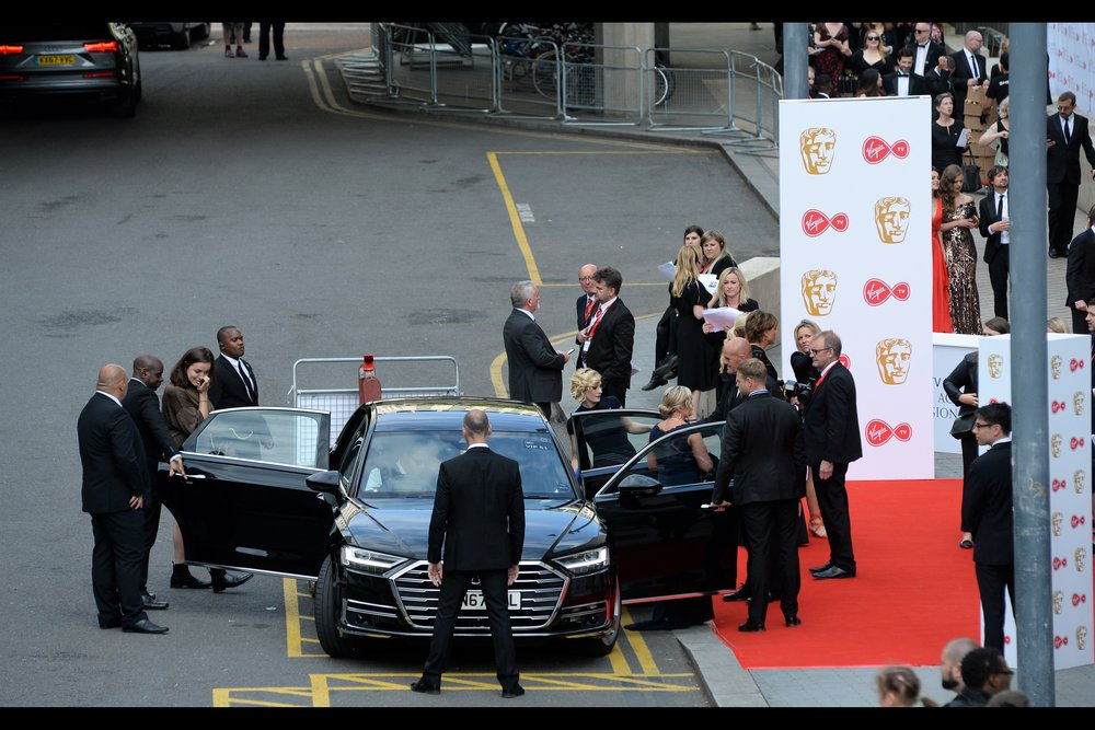 The lady exiting at the back of the car is Jodie Whittaker : the current (upcoming?) incarnation of Doctor Who.