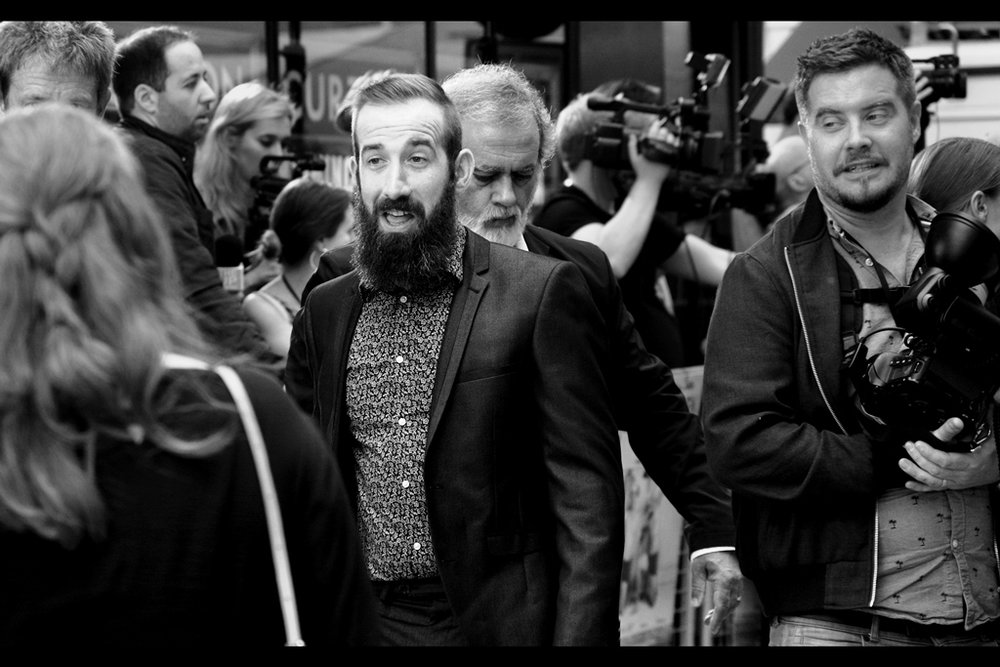 """You don't need to see my ticket. Just check out the beard"" . It is quite the beard. Man on the far right thinks his shirt is one of those Magic Eye things that were all the rage in the 1990s."