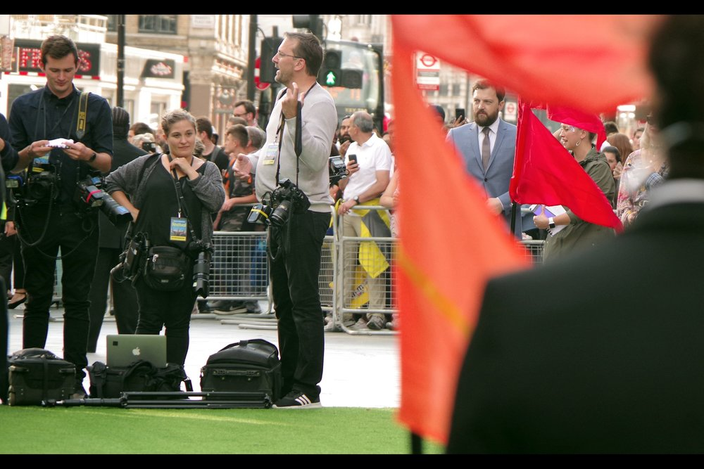 "Director Iain Morris, either artfully or coincidentally framed by the festive ""festival"" flags placed at the edges of the carpet to provide added autofocus challenge for my Pentax (as if errant air particles and the camera's ditzy ""charms"" weren't enough)"