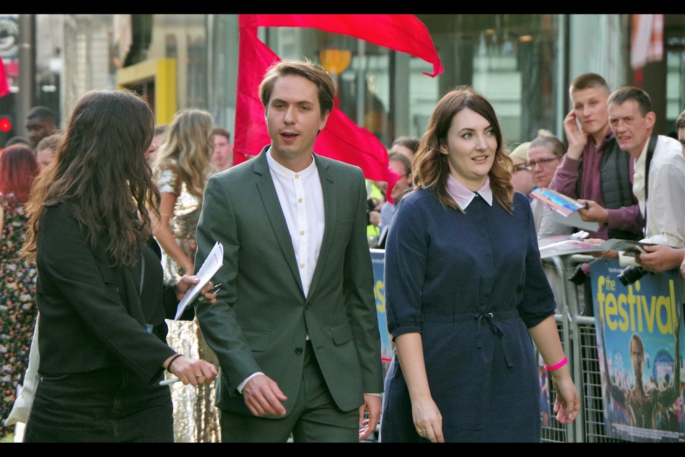 """Ties? Who wears ties in the 21st Century?? I'm a Millennial - you're lucky I'm even punctual""  Joe Thomas was in 'The Inbetweeners' and 'The Inbetweeners 2' movie... as well as this movie, which I totally recall is<rechecks> ""The Festival"""