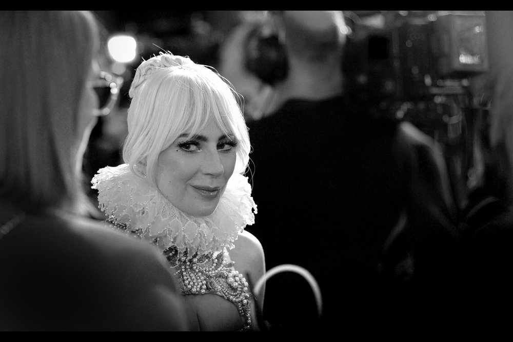 """Nice one, Janice"" - There reason why I'm posting so many black'n'white shots of Lady Gaga is because while she's wearing a dress that I'm laughably calling ""subtle"", her assistant (front left in this photo, front right in the prior one) is wearing a dress that's on the PINK side of BRIGHT CRIMSON. Nice one, assistant Lady."