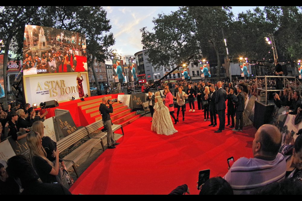 With not one but two bouquets of flowers thrown into the crowd by Lady Gaga, Aussie-Rules style (with apologies to 99% of the planet to whom this means little), the final (and possibly) best angle for my spot in the pen is about to be revealed. At 90% of premieres, the interview subject stands on the left side of the host… and that's (a) seemingly the setup here, and (b) where the space is…. but I really need for her to stand on the RIGHT of the stage.