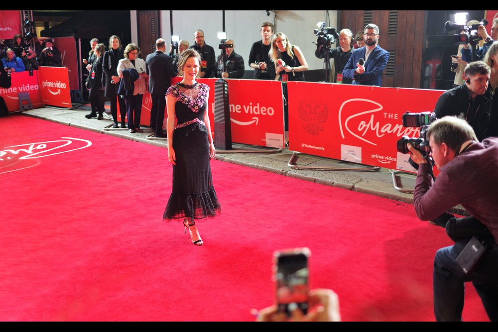"""Pose, baby! POSE! No, not for me with the camera, but for the mobile phone on my left. That guy clearly wants the photo more""  Rachel Brosnahan, contrary to what appears to be some pretty bad compositing, is actually at this premiere and has not merely been carelessly placed so as to hover just above the red carpet."