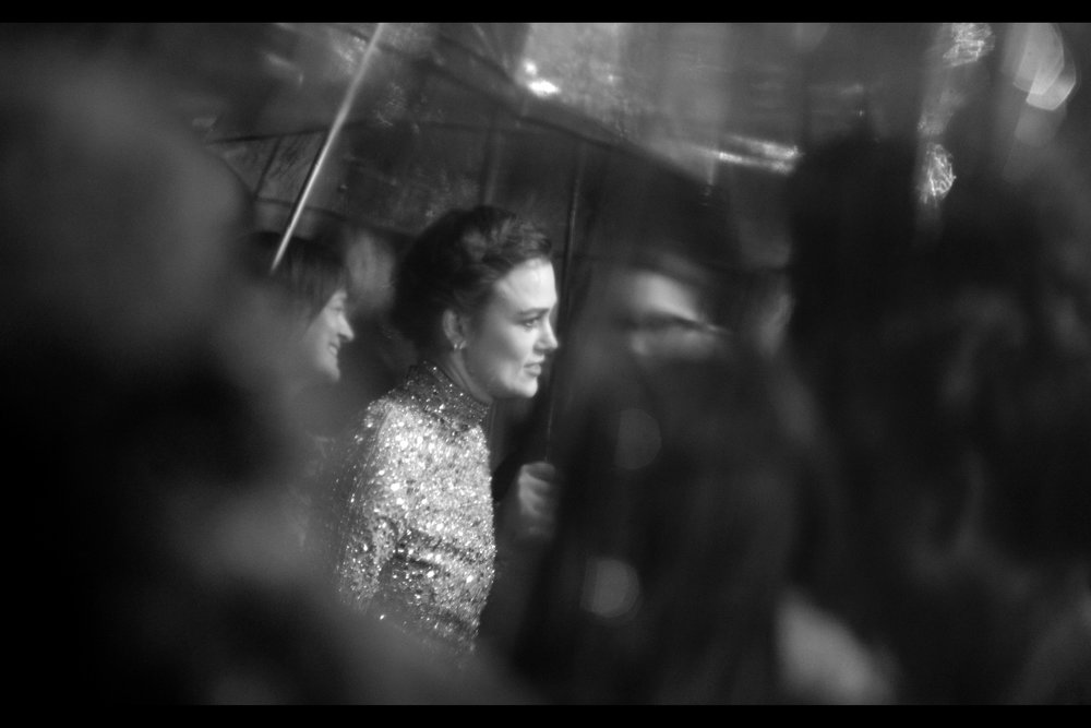 Keira Knightley in dream-o-rama <TM> - photographed through multiple semi-rain-slicked umbrellas held by the interview media… even though it has by now mostly stopped raining.