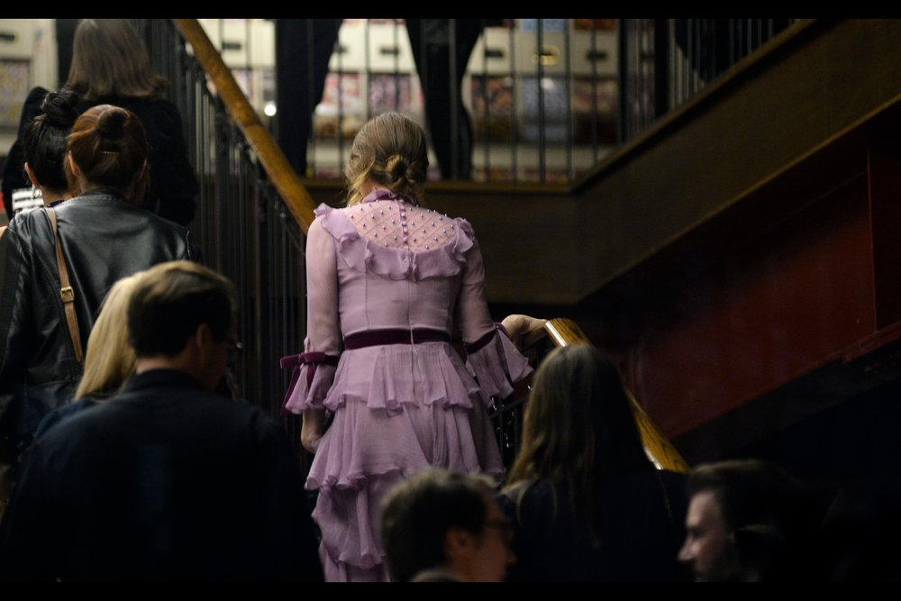 Zoe Kazan's Dress, walking up stairs. You know what would be nice…. having photographers at the bottom of the stairs, and having her turn around and pose on the staircase, with the chanedeliers above providing cool lighting and visuals.