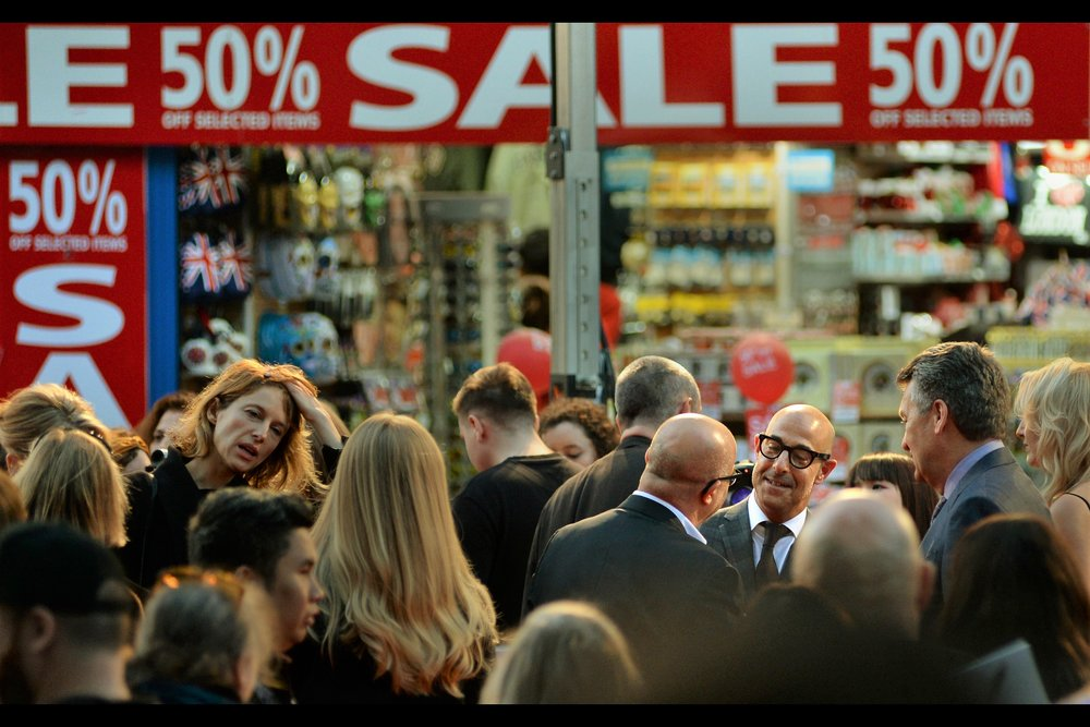 """Stanley Tucci, bottom right :  """"I don't care, as long as I'm framed by Leicester Square's iconic 50% SALE signs!!""""  - and it's an angle none of the Paparazzi are covering, so it's lucky I'm here."""