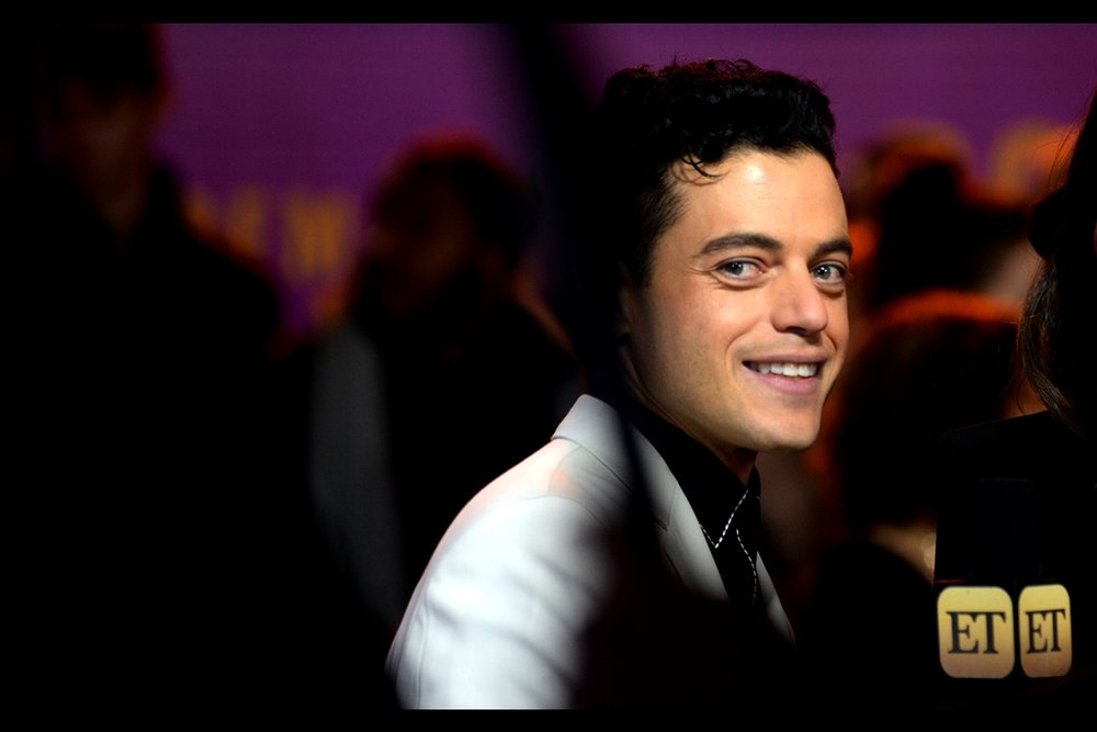 "I was pretty close to deleting the dual 'ET' signs on the interviewer's microphone, but this mid-range shot that somehow the people in the pen were too cool / oblivious to see was mainly due to them. Also : Rami Malek seems very nice : I've photographed him only once before, as a guest at    the ""Lost City of Z"" premiere   ."