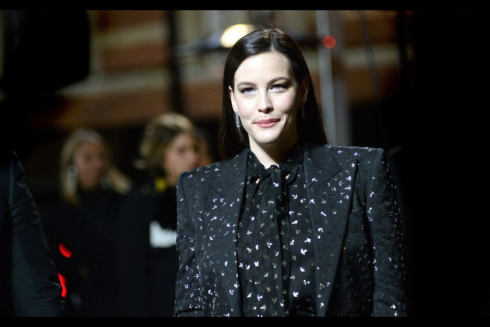 It's Liv Tyler! I once had a Uniqlo t-shirt with a kind of a glossy-black-on-matte-black design. The gloss slowly wore away, sometimes dispensing little bits o'black all over any other shirts in the same washload. True story.