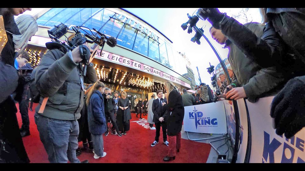 I'm using the quirky 360 degree Ricoh Theta on this shot, not just because I like it as a gimmick, but because I've noted that, just like any proud father, Andy Serkis has angled himself in front of the paparazzi cordon to photograph his son being interviewed by Edith Bowman.