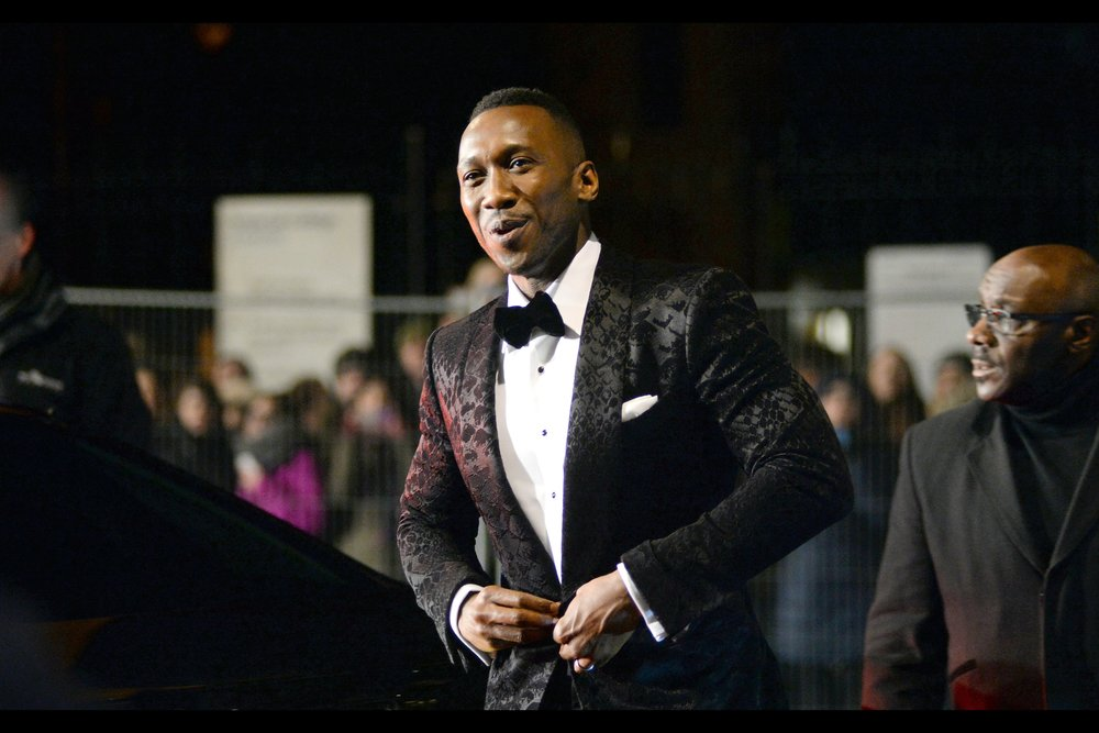"""No way I'm telling you where to get this jacket. First, the fact that you want it suggests you have good taste, which is why I think it's important that you NOT be able to get your hands on it and dilute the cool factor"".  Eh… my choice of beanie at this event probably deserved that. This is Mahershala Ali - he won an Oscar for Best Actor for 'Moonlight' and he's also in    Alita Battle Angel (though he wasn't at its premiere)      -    edited to add he won Best Supporting Actor for 'Green Book' on the night."