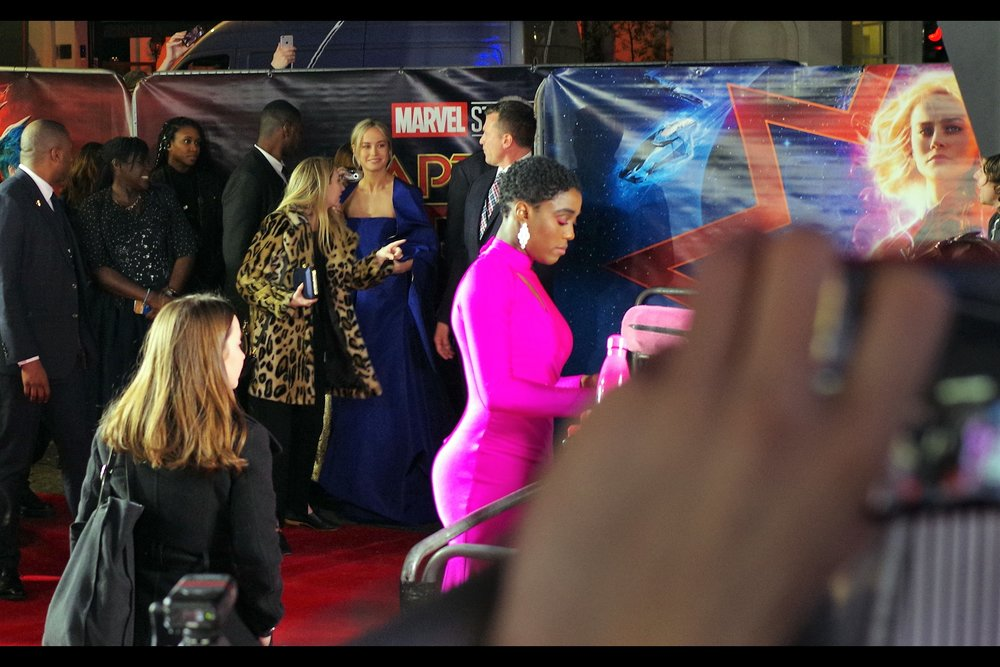 Behind a pink so searing my camera's sensor wasn't quite sure what to make of it (worn by Lashana Lynch, who is in this movie), and next to a lady wearing a leopardskin (print?) jacket…. it's kind of hard to appreciate the importance of that fact that Brie Larson, who plays the titular Captain Marvel, has arrived.