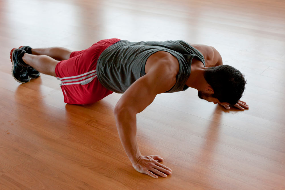 stock-photo-attractive-muscular-man-doing-push-ups-on-a-wooden-floor-92854840.jpg