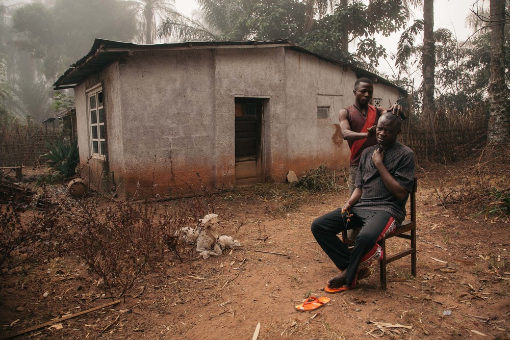 After leaving the pirogue to a village on the river we struggled on by bicycle to the Bilomba Catholic mission. One of the brothers shaves the head of an elder father in the courtyard.