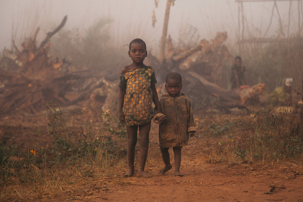 A young boy is lead by his older sister back to their home on the roadside.