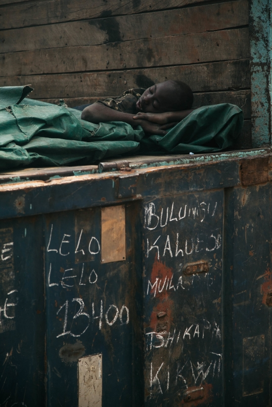 A boy takes a rest in a recently unloaded truck. Names of towns on the trucks passage are marked on the back door.