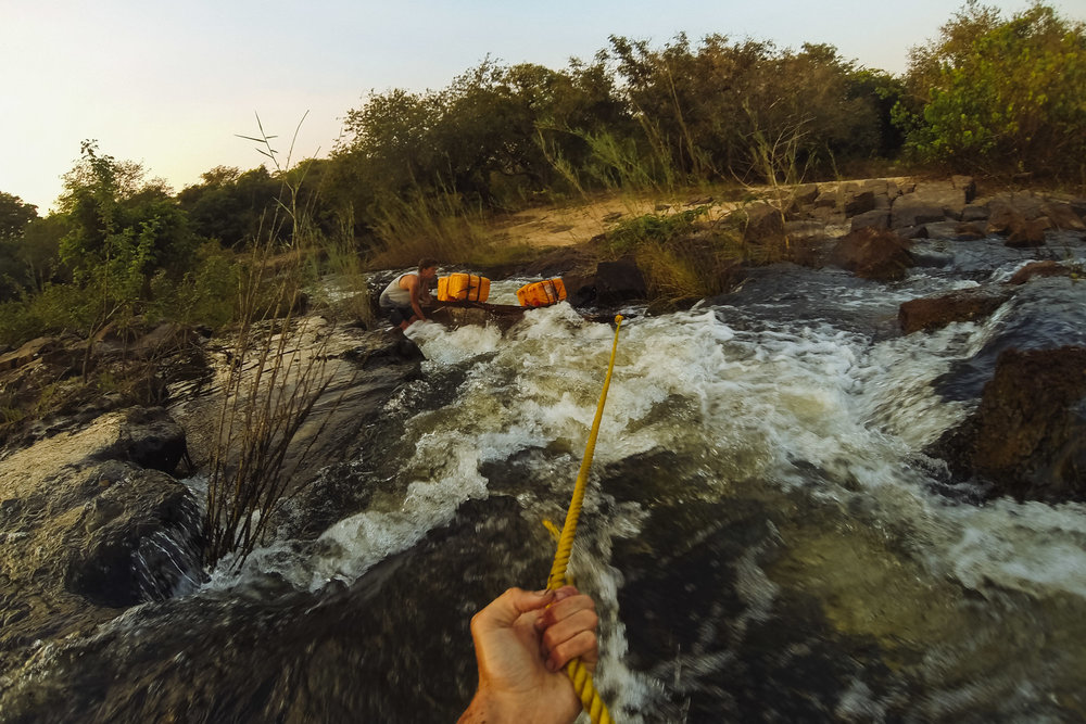 Charlie acts as anchor whilst I guide the the pirogue through a narrow set of offshoot rapids.