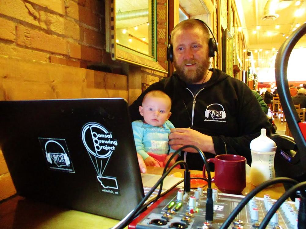 "Station Manager  Eric Waier running the board, along with his daughter, for the weekly broadcast of ""Birds On A Wire"" which is live broadcast every week from MT Coffee Traders in Whitefish."