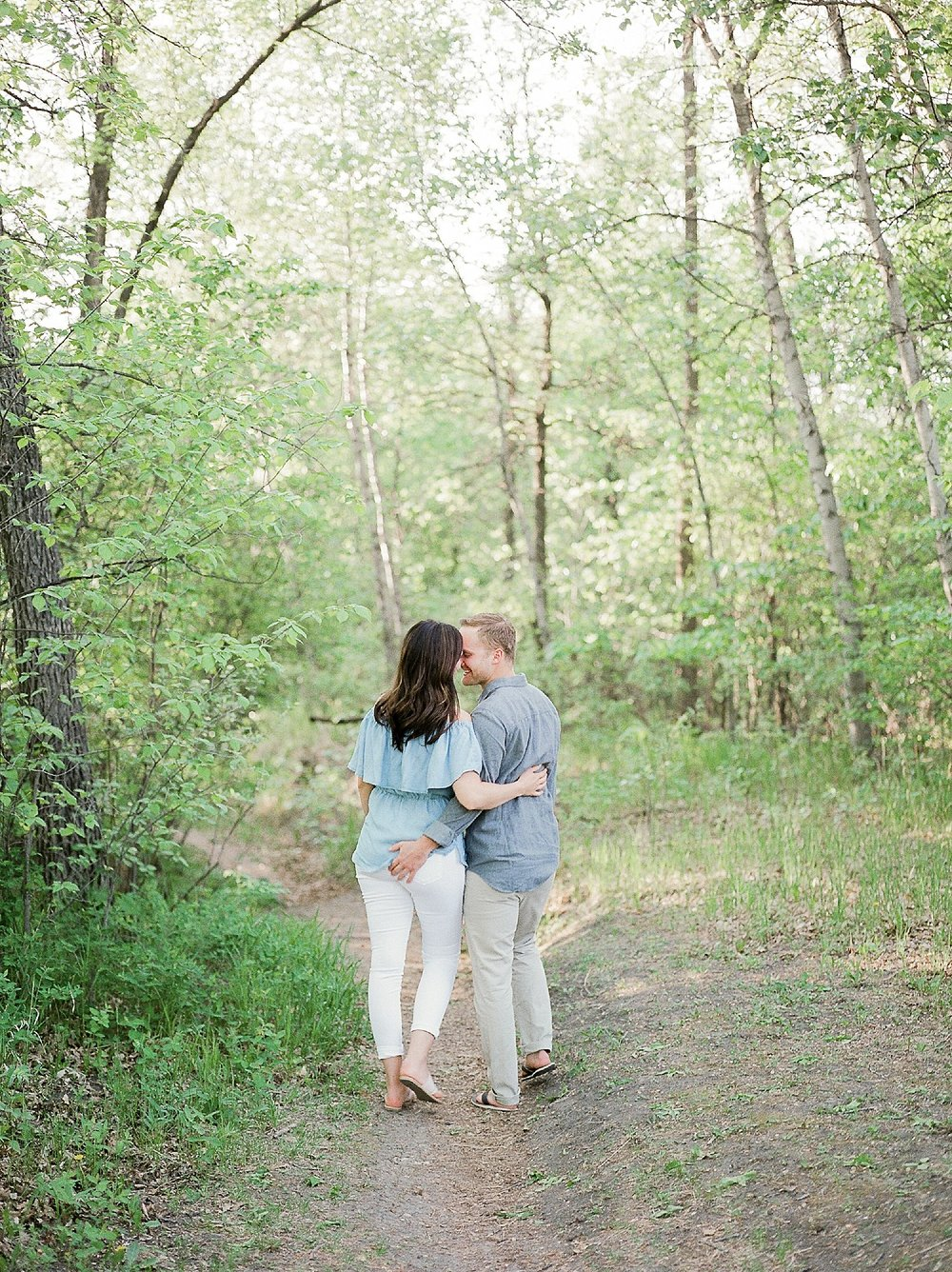 fun engagement photo poses, engagement session outfit ideas for summer, engagement photos at a park, kings park winnipeg, denim over the shoulder top,