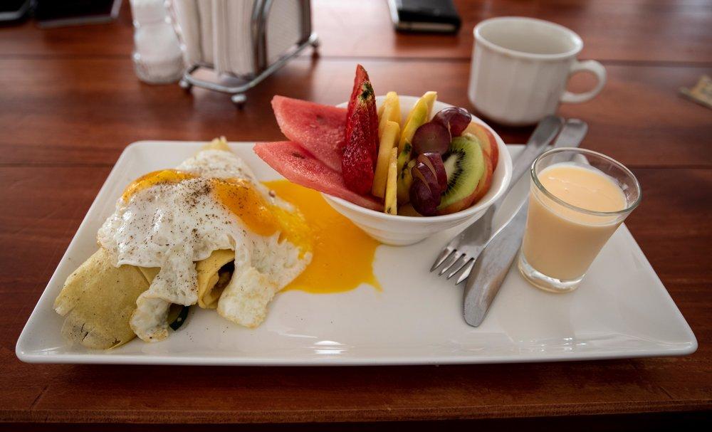 Breakfast. Savory vegetable crepe, fresh fruit and yogurt.