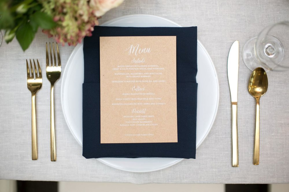 Custom Wedding Menu by Sable and Gray - white ink on kraft card stock, with navy napkin and gold flatware.