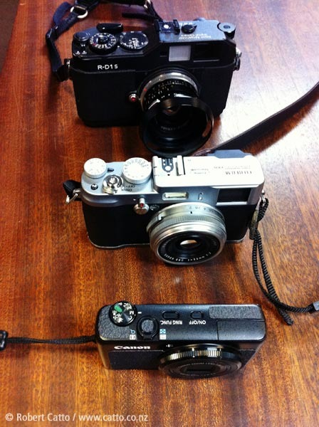 From the top - my Epson R-D1s (same size as a Voigtlander Bessa) with a Leica Summilux 35mm pre-ASPH, the Fujifilm X100, and my Canon S90.  So, the X100 isn't huge, but it isn't tiny either…  (Shot with my iPhone, naturally!)