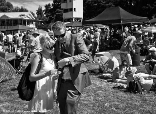 Took this at the races in  Tauherenikau  on Jan 2 this year - I like it because it kinda sums everything up from that day.  He's got a new suit (with a bit too much stuff in the pockets, and the tag still on the sleeve), she's got a glass of wine AND a bottle of water, there's money coming out of his wallet, they're checking their ticket from the last race, and around them are crowds, gazebos, tents, umbrellas, folding chairs, people lying in the sun…it's all there.  And it was!