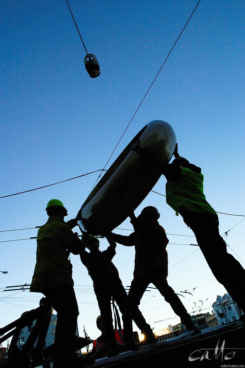 Crew from Weta Workshop lift a giant ring aloft outside the Embassy Theatre in Wellington
