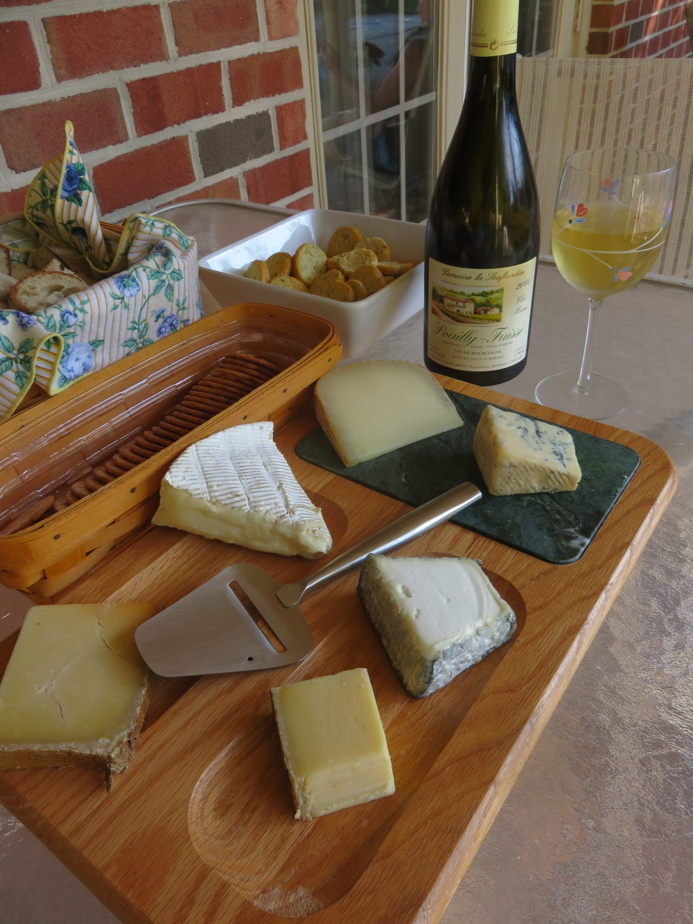 Starting from closest to the wine bottle and moving clockwise: Ossau-Iraty, Bay Blue, Valençay, Comté, Beaufort, Brie
