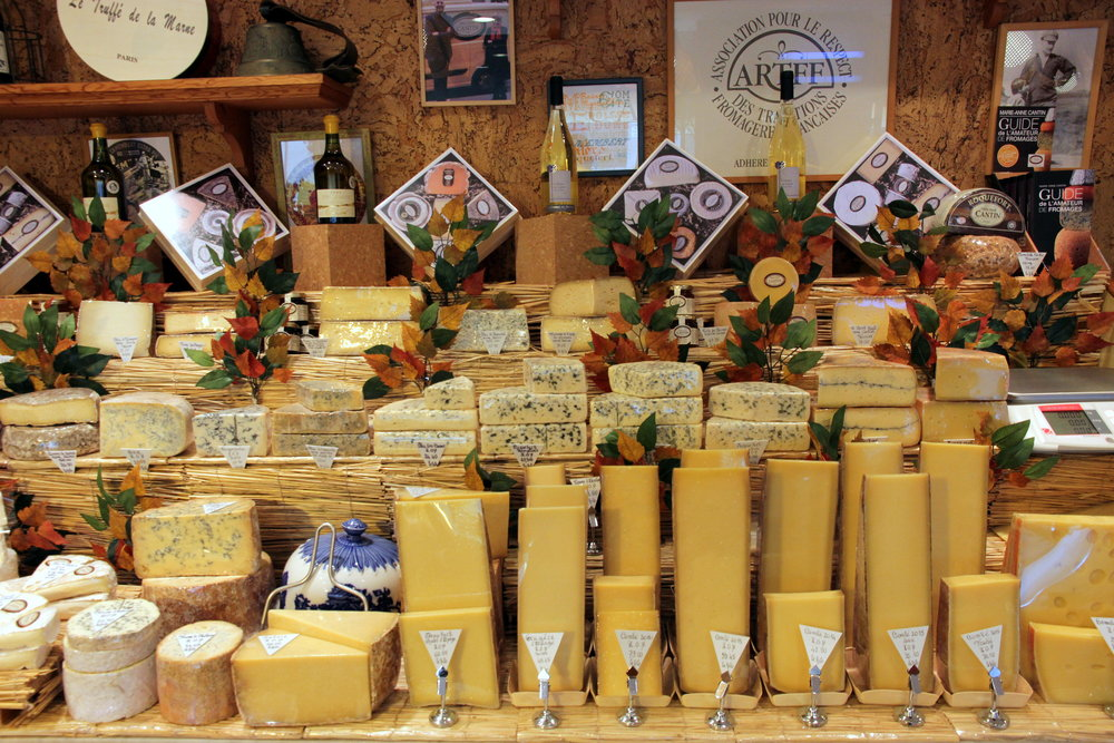 A picture from Fromagerie Cantin in the 7e arrondissement of Paris. Marie-Anne Cantin is a second generation affineur and comté is one of her hallmarks. Of the seven tall soldiers in the bottom right of this picture, the five right-most are comtés ranging from 2012 to 2016.