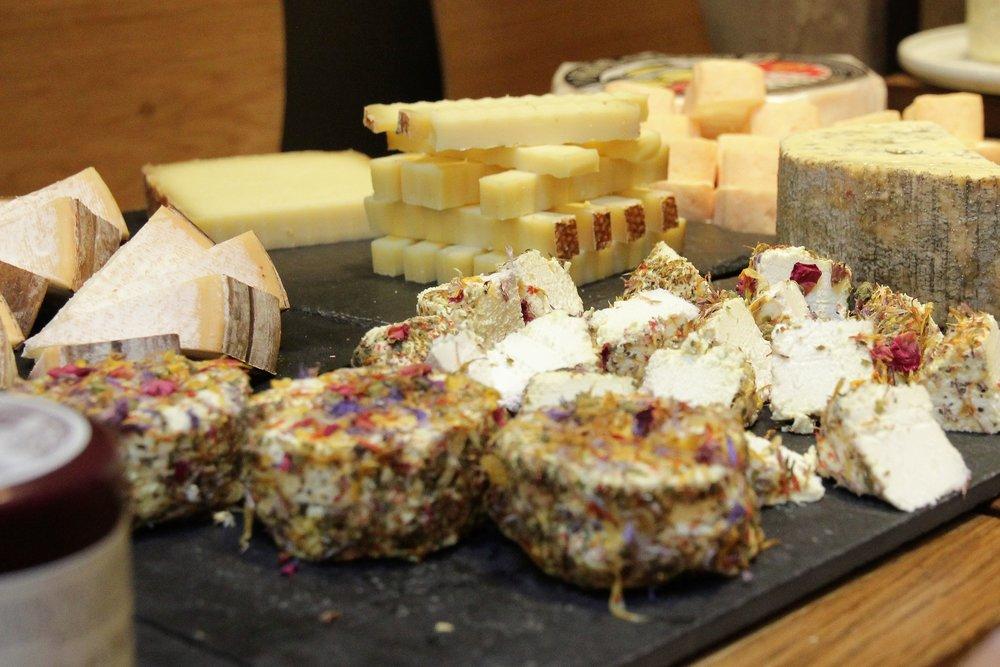 Un fromage de chèvre incrusté de pétales de fleurs. Un peu bizarre, mais pas mal quand même. Du gruyère derrière.