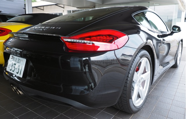 Black Porsche Cayman S, from the side rear