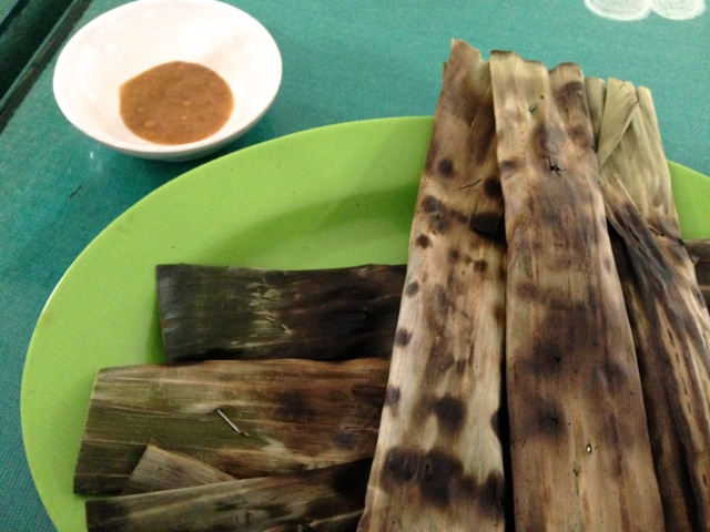 A kind of kamaboko (fish paste) roasted in banana leaves, served with a sweet peanut sauce