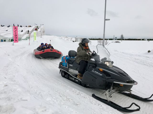 Ride a raft behind a snowmobile