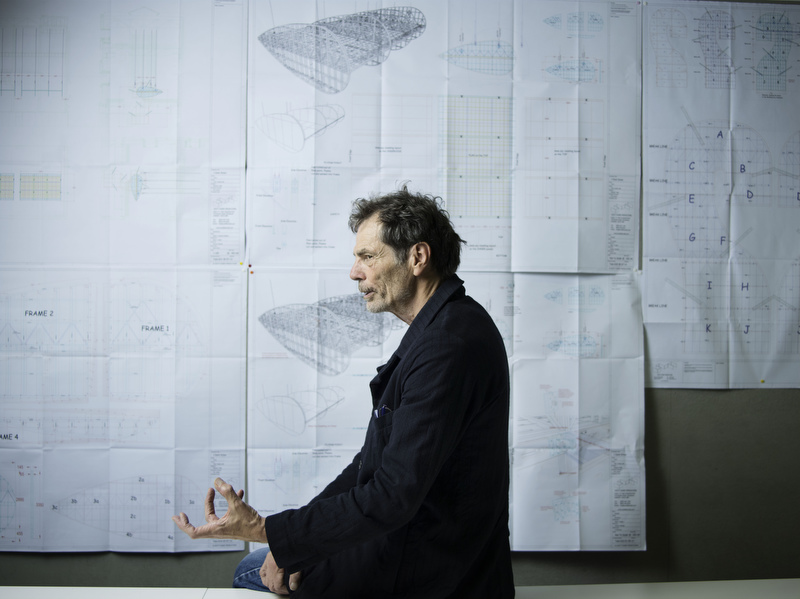 Richard Tuttle poses in front of plans of the structure of his installation in the turbine hall of the Tate Modern gallery.
