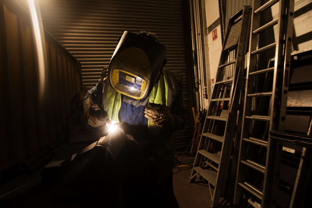 A National Express welder at work repairing parts for one of the companies coaches  at their Garage in Heathrow, London.
