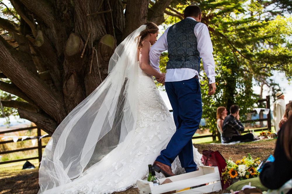 bride and groom walk under tree