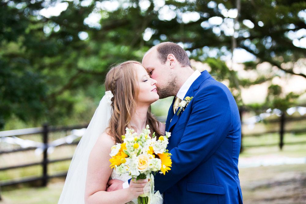 groom kisses bride under tree