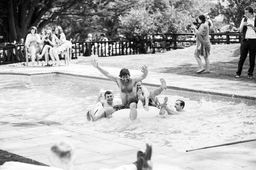 groomsmen splash in swimming pool