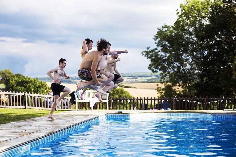 groomsmen jump into swimming pool