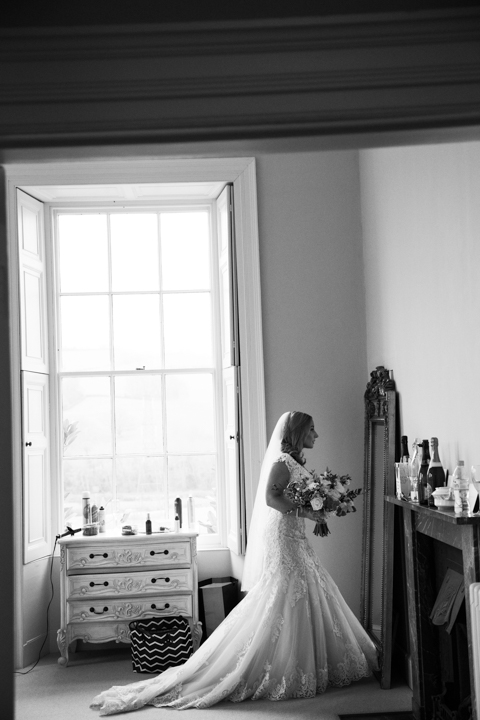 side view of bride looking in mirror wearing wedding dress