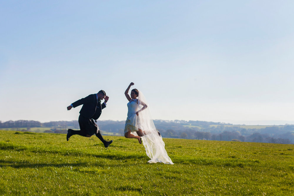 bride and groom jump for joy