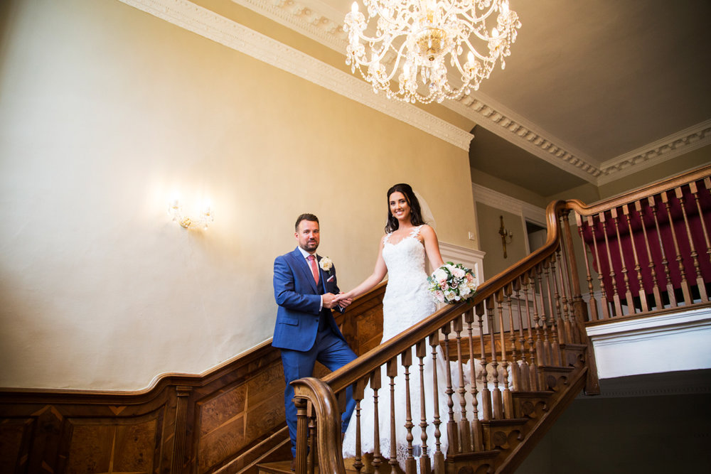 bride and groom on stairs at Kingston Estate Devon