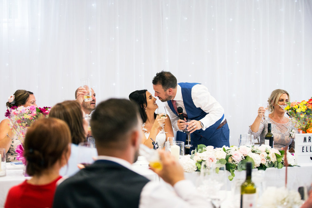 groom kisses bride after speech Kingston Estate