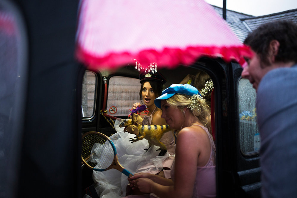 bride and bridesmaids in black taxi photo booth