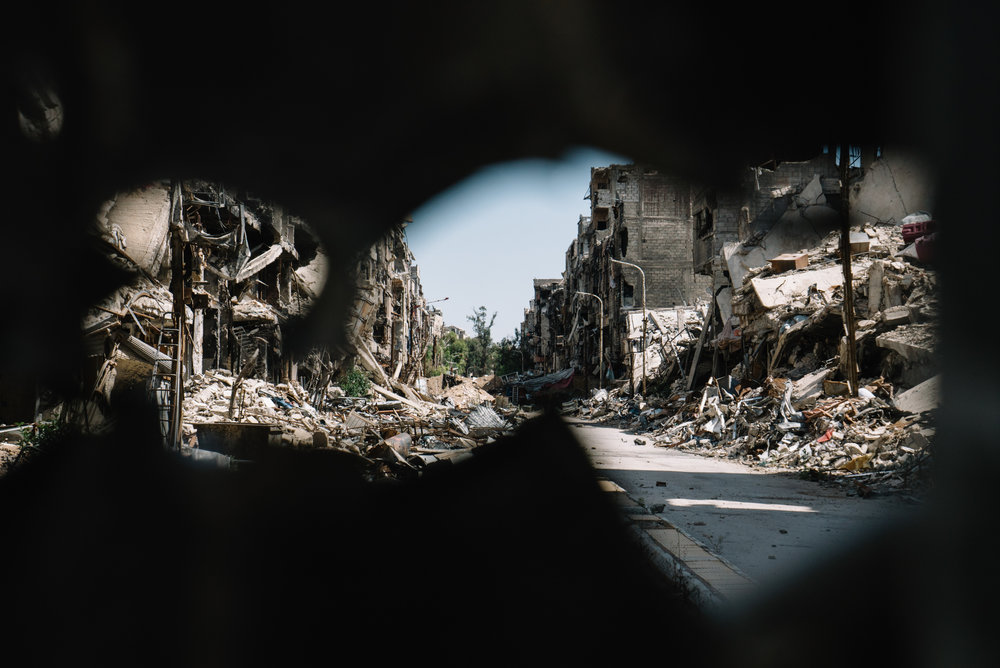 Looking through a hole in the (quiet) frontline between PFLP militias and Jabhat Al-Nusra in Yarmouk. | Damascus, Syria - May 2016