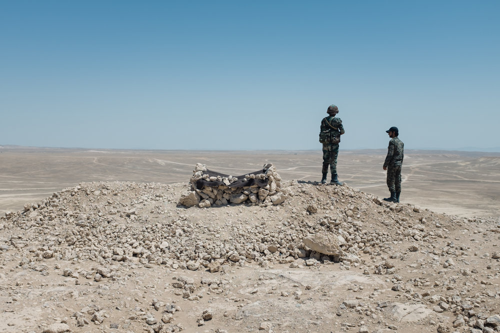Syrian government soldiers look across the barren desert, scanning for suicide car bombs and signs of ISIS troop movement. | Eastern Homs Province - July 2016