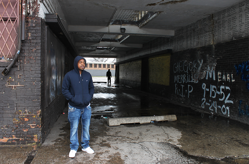 Altgeld Gardens resident Antonio hangs outside a convenience store in a dingy alleyway in the complex.