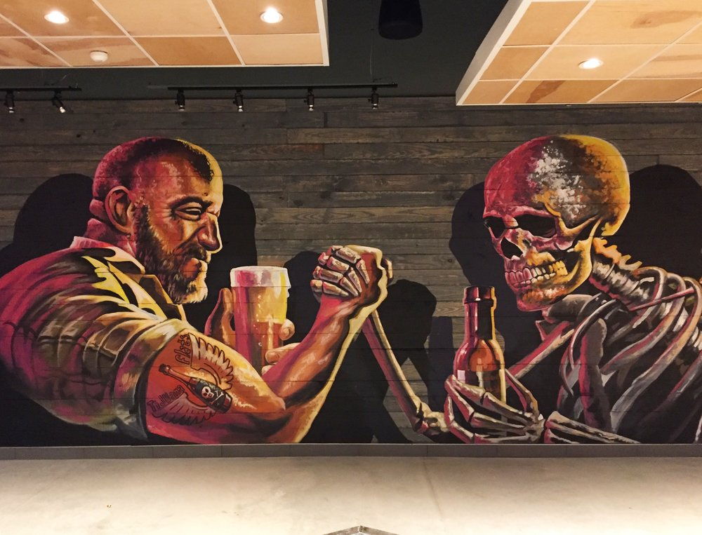 A mural of a man arm wrestling a skeleton in Tijuana Flats.