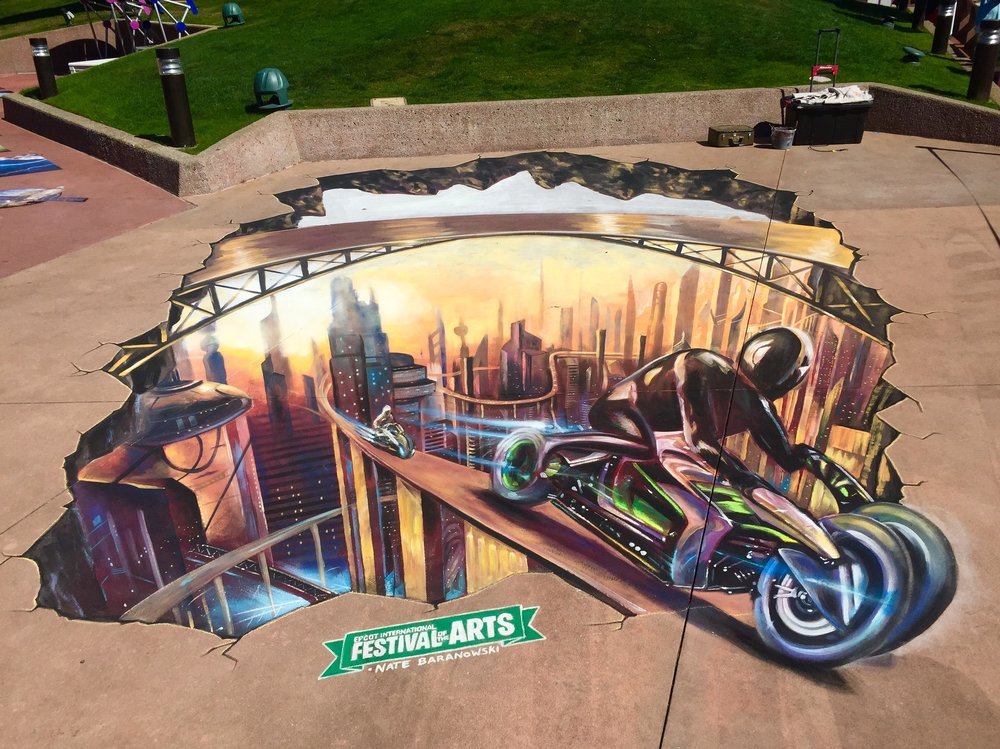 A futuristic city inspired by Tron created in chalk at the 2018 Epcot International Festival of the arts. 3D street painting.