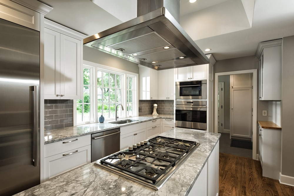 After: Cooktop integrated with usable workspace and ventilation on the island. Multiple ovens stacked in an integrated cabinet column. Easy triangle flow from sink to cooktop to ovens, with room for a mixer and a dough slab in between.